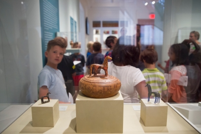 Local students observing a collection of ancient bronzes and a pyxis